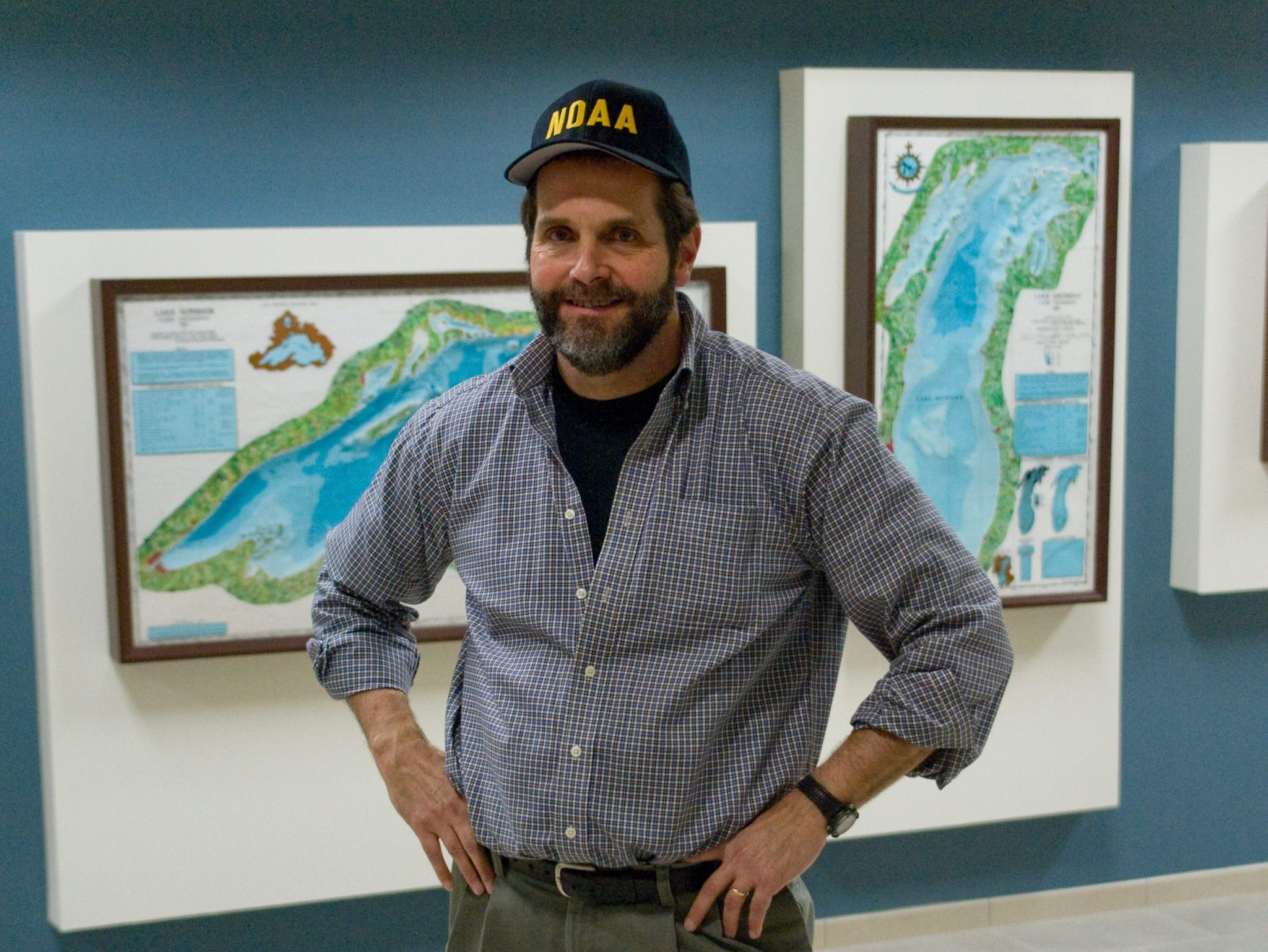 A man in a baseball cap stands in the GLERL lobby in front of some 3-d bathymetry maps of the Great Lakes