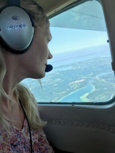 A woman sits in a small airplane with headphones and a mic on, looking out the window at a bay on Lake Michigan Below.