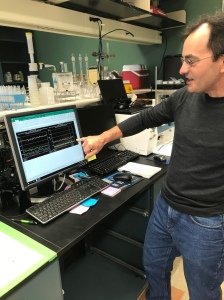 A man in a laboratory points at graphs on a computer screen.