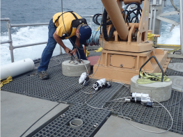 photo of many on boat bending over and working on scientific instrument